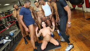 Brown-haired whore gets on her knees to suck off a bunch of black cocks