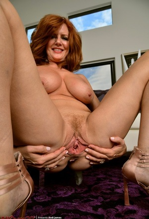 Older redhead Andi James stretches open her vagina after lingerie removal