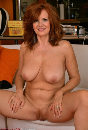 Mature redhead Andi James showcases her pussy in the nude