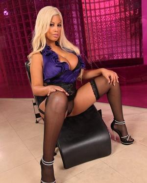 Stunning platinum-blonde Bridgette B reveals her massive big boobs posing in high heels