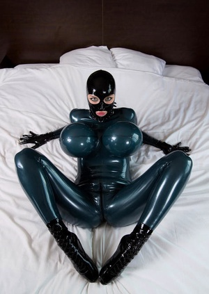 Clothed female models on bed with curtains open in rubber bodysuit and hood