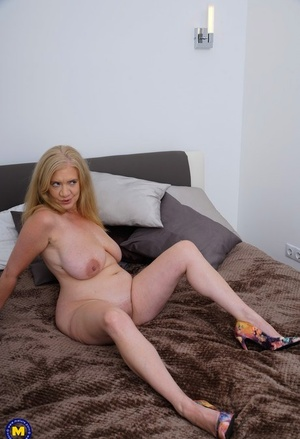 British granny with big naturals rides on top of her toy man on bed