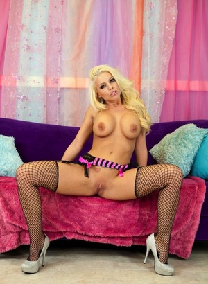 Blonde solo woman Britney Amber shows her big tits and twat in mesh nylons