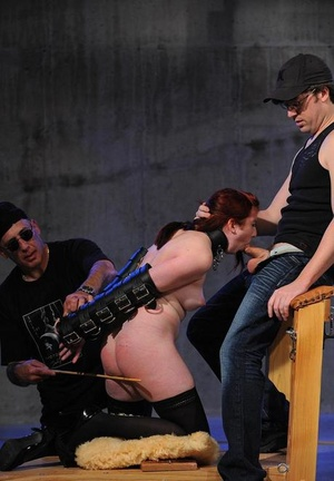 Redhead female is made to suck a cock while being caned at the same time