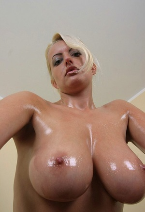 Blonde chick Arabella Bella oils up her large tits during closeup solo action