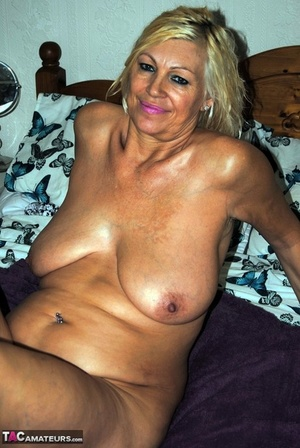 Mature fatty Platinum Towheaded lounges nude to display oiled big floppy tits